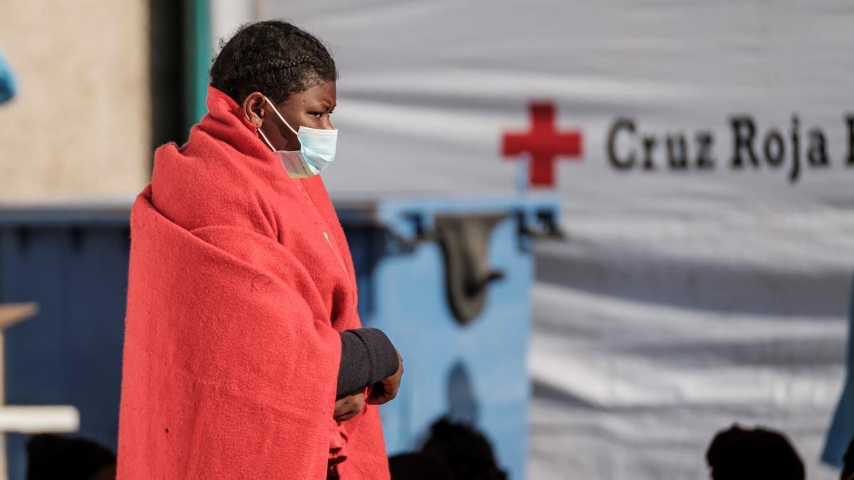 Una mujer rescatada de un cayuco al sur de Gran Canaria camina en el muelle de Arguineguín