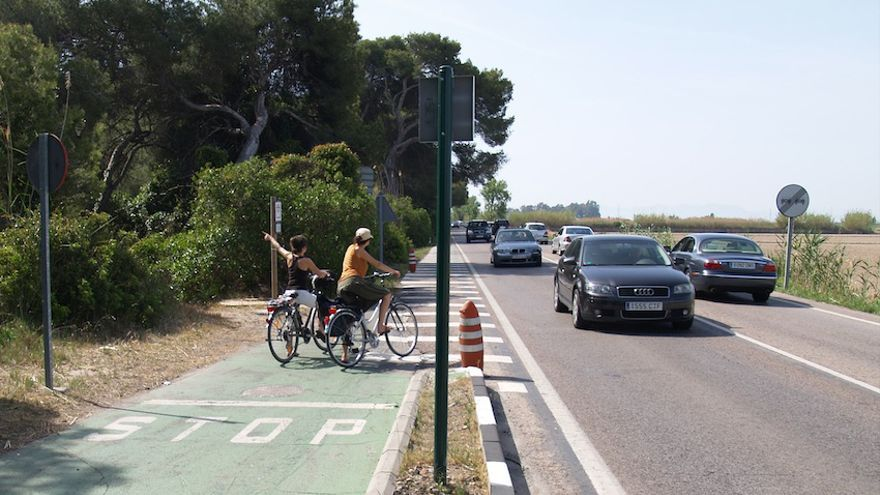 Dos ciclistas esperan para cruzar la CV-500, en el Saler