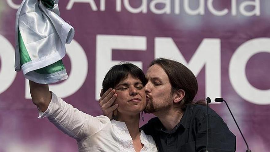 Pablo Iglesias besa a Teresa Rodríguez en un mitin, mientras ella sostiene la bandera de Andalucía.