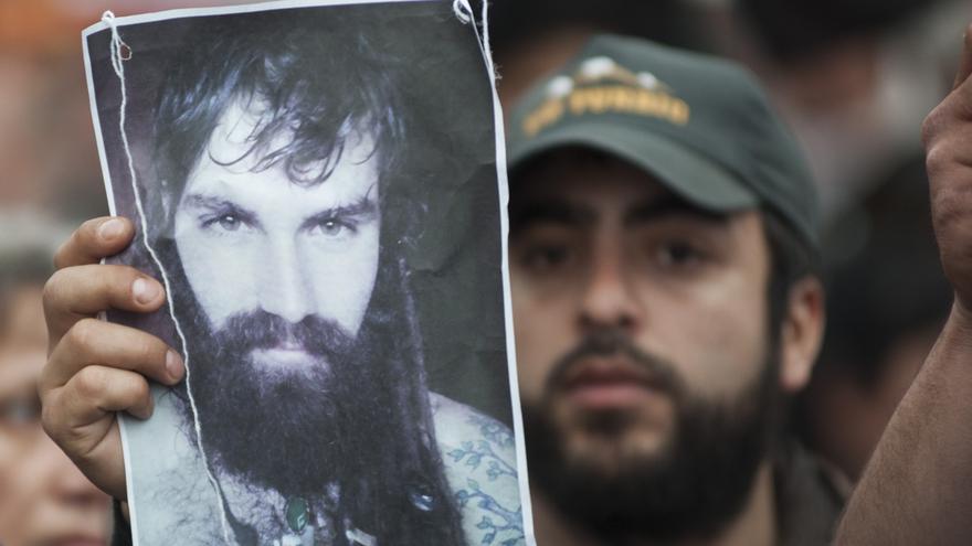 Un manifestante sostiene la fotografía de Santiago Maldonado, el artesano desaparecido durante una protesta indígena en la Patagonia argentina.