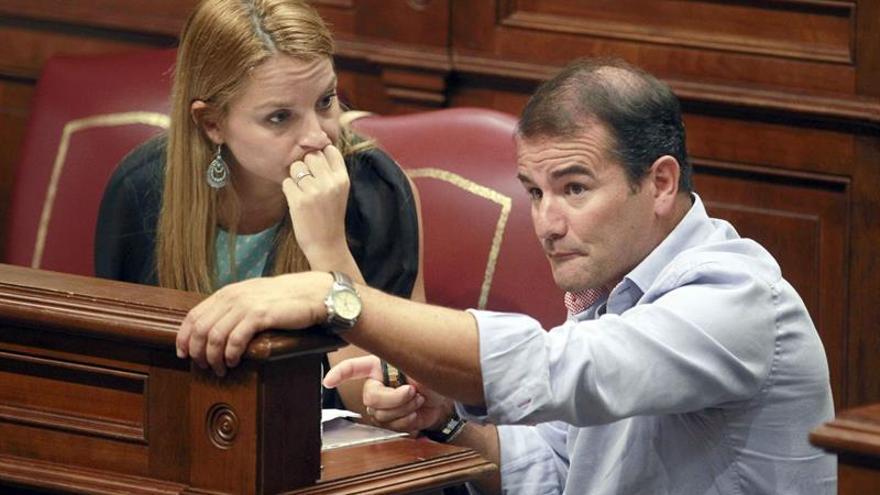 Los diputados Noemí Santana, de Podemos, y Marcos Hernández, del PSOE, conversan durante el pleno del Parlamento de Canarias. (Efe/Cristóbal García).