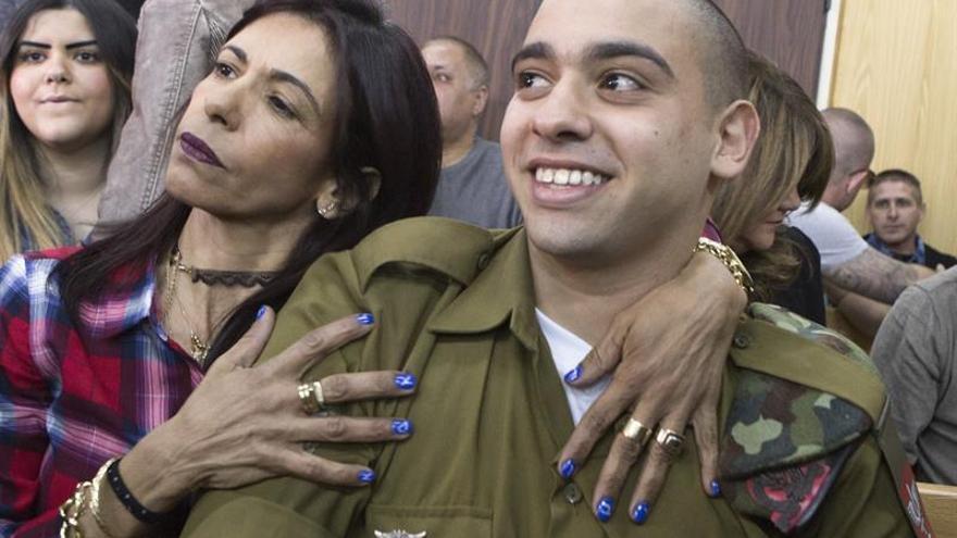 El soldado israelí Elor Azaría (d), es abrazado por su madre antes de escuchar el veredicto del tribunal militar israelí que lo ha juzgado en Tel Aviv, Israel.