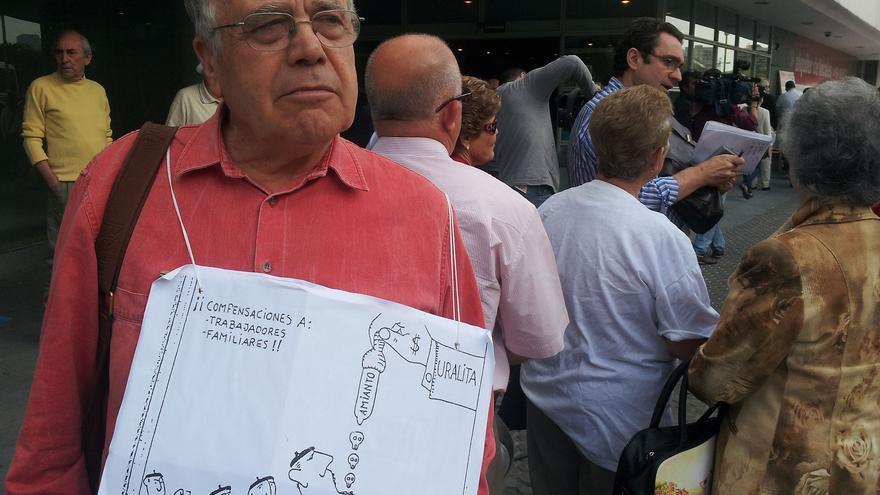 Francisco Jiménez, uno de los afectados, porta un dibujo que denuncia la situación por la que pasaron los trabajadores de Uralita.