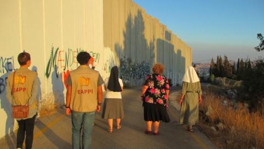 Monjas y voluntarias caminan pausadamente mientras rezan el rosario, recorriendo el pequeño tramo de pared gris que va desde el 'checkpoint' | WCC/EAPPI