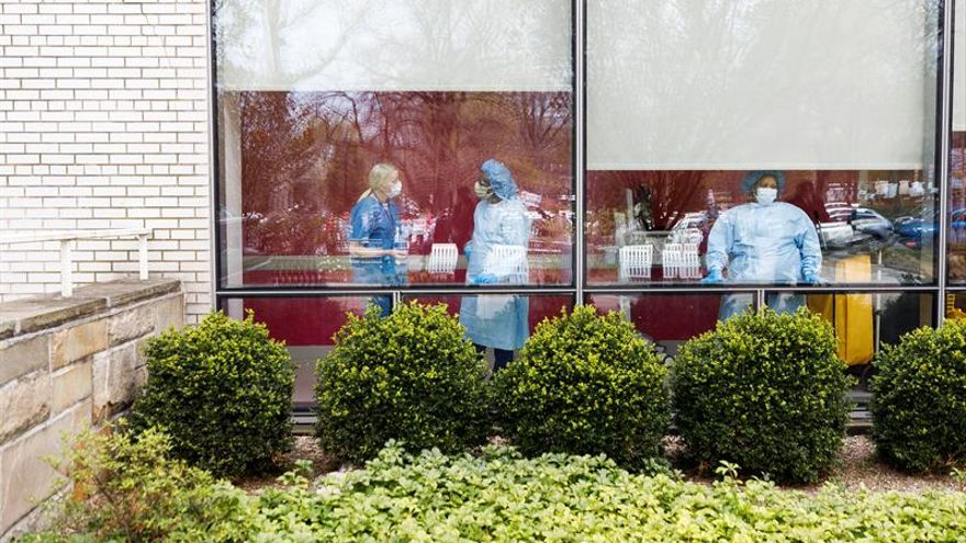 Healthcare workers stand a window at Jacobi Medical Center as nurses rally to protest their lack of personal protective equipment, PPE, and institutional support in the Bronx, New York, USA, on 17 April 2020.