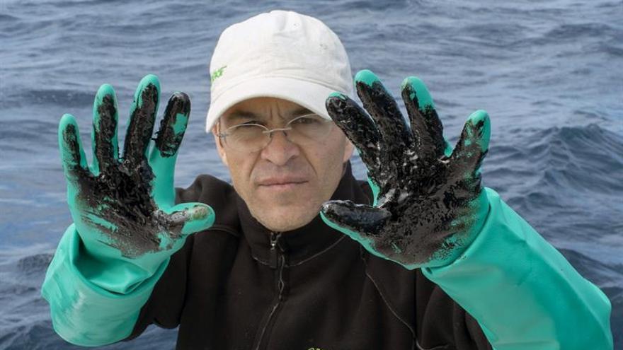 Uno de los miembros de Greenpeace que se han desplazado junto con expertos de la Facultad de Ciencias del Mar en la Universidad de las Palmas en un barco hasta la zona del hundimiento del 'Oleg Naydenov'. (EFE/Greenpeace)
