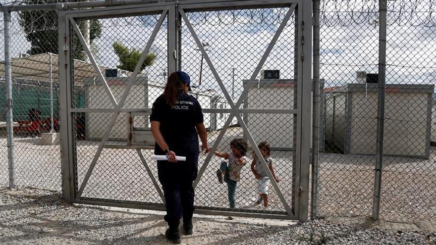 Una agente de policía conversa con dos niñas refugiadas iraquíes al otro lado de una valla, en el centro de detención de inmigrantes indocumentados de Amygdaleza, en Atenas, Grecia. EFE/Archivo