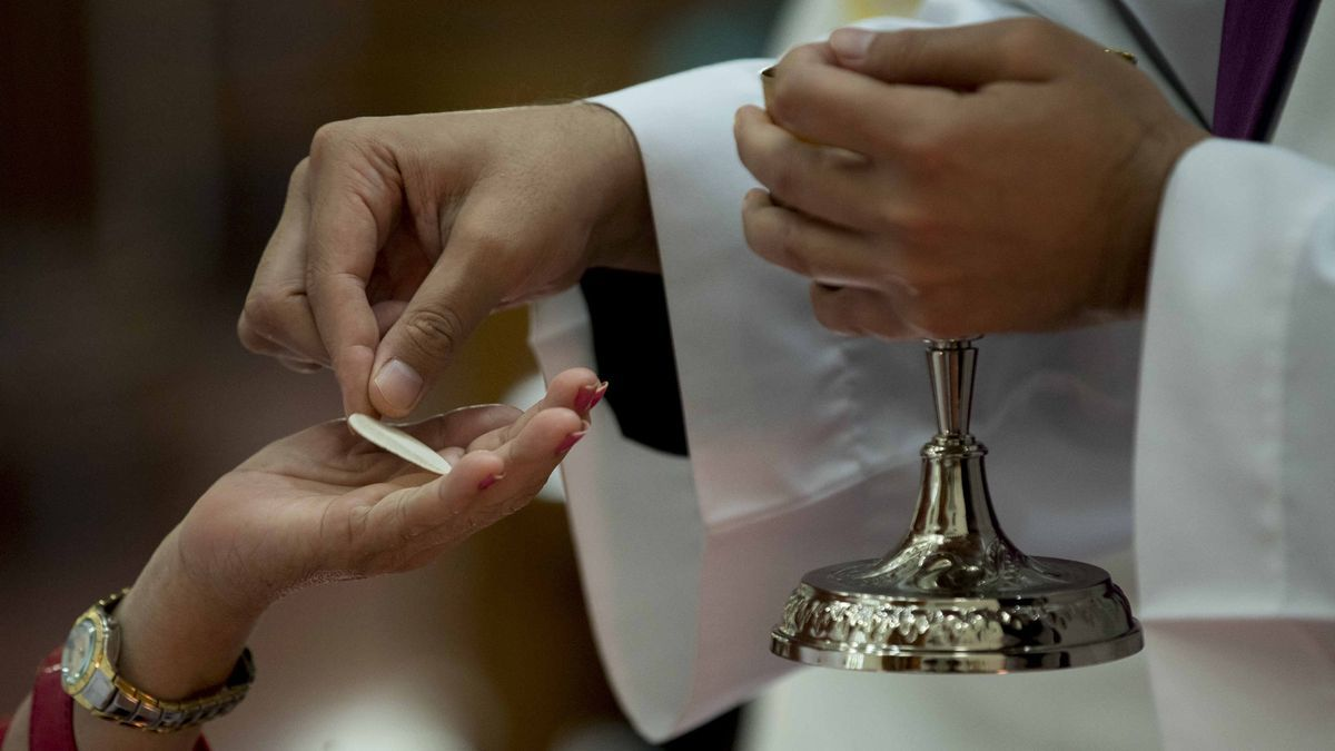 Una mujer recibe la hostia durante una misa.