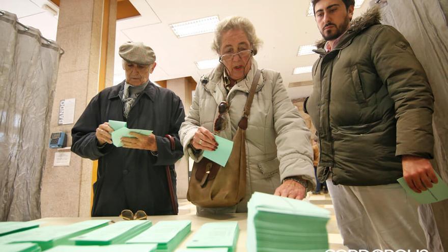 Votantes frente a una mesa con listas electorales de los partidos | ÁLEX GALLEGOS
