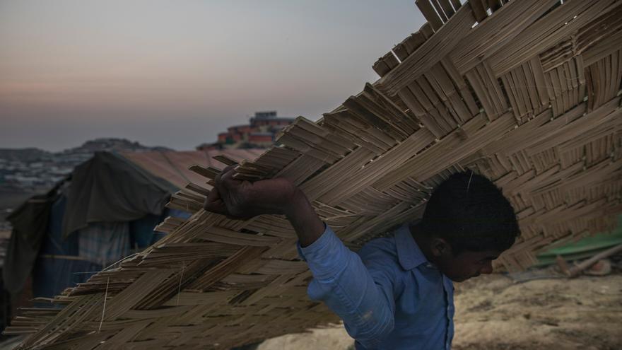 Un niño cargando bambú en el asentamiento improvisado de Jamtoli.