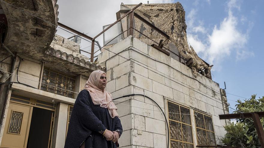 Manal posa delante de la casa en la que vive con su familia en Hebrón, y donde el ejército israelí ha instalado una torreta de control en su tejado.