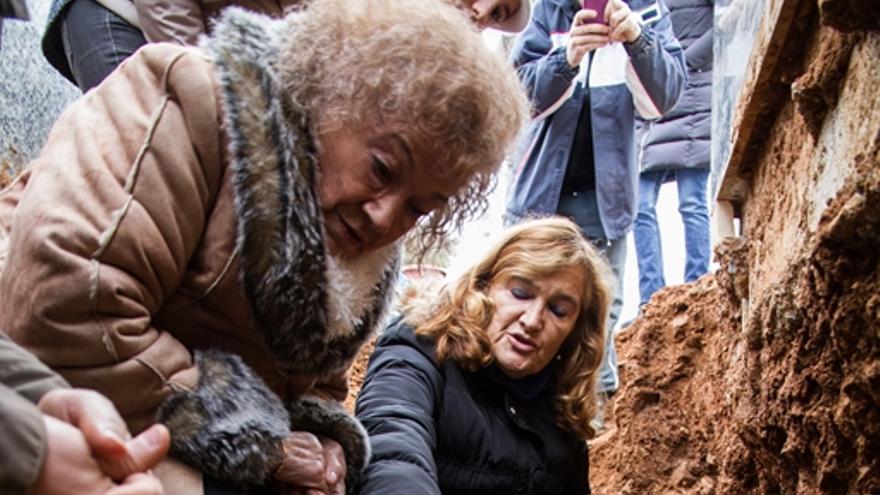 Milagros y su hija Pilar contemplan los restos mortales de Vicenta en la fosa anónima donde fue enterrada sobre su hijo Jesús / ARMH