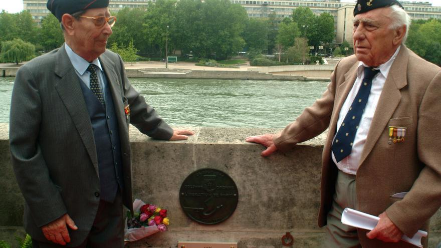 """PARÍS-ANIVERSARIO/COMBATIENTES ESPAÑOLES:PA05. PARÍS, 24/08/04.- Los combatientes Luis Royo (dcha.) y Manuel Fernández (izqda.) posan junto a la placa conmemorativa de la compañía llamada """"La Nueve"""", durante el homenaje que recibieron hoy los republicanos españoles que participaron en la liberación de París. """"La Nueve"""", compañia compuesta esencialmente por españoles, entró en París el 24 de agosto de 1944, como avanzadilla de la división mandada por Leclerc, que penetraría al día siguiente en la capital y la liberaría con el apoyo de tropas estadounidenses de la ocupación nazi. EFE/JORGE SCLAR"""