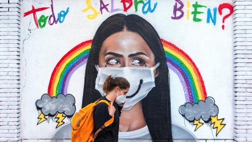 Una mujer pasea frente a un mural en Barcelona