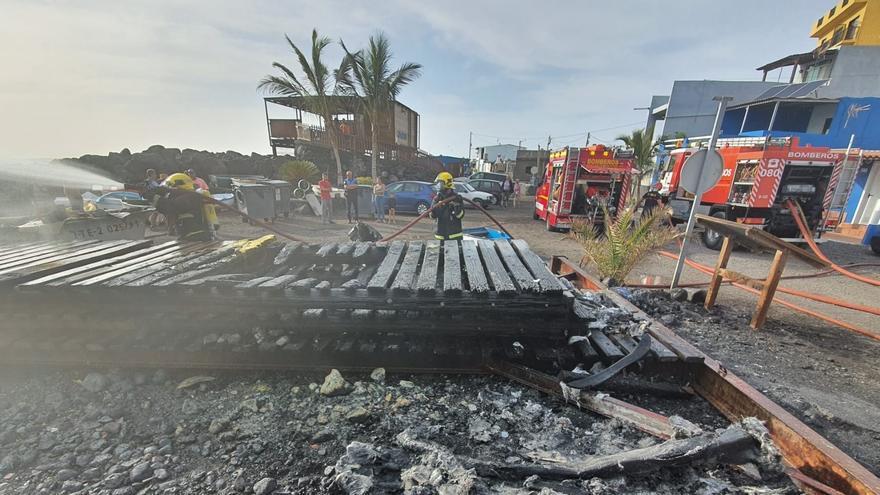Dos bomberos actuando en la zona donde se ha registrado el incendio de dos embarcaciones en el núcleo costero de La Bombilla en la tarde de este jueves.