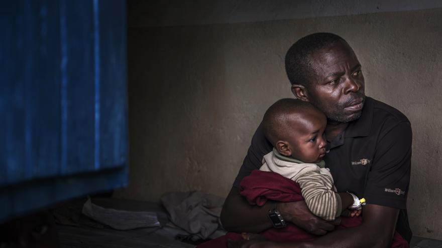 Un padre coge a su hijo en brazos. El niño se está recuperando gradualmente del cólera.