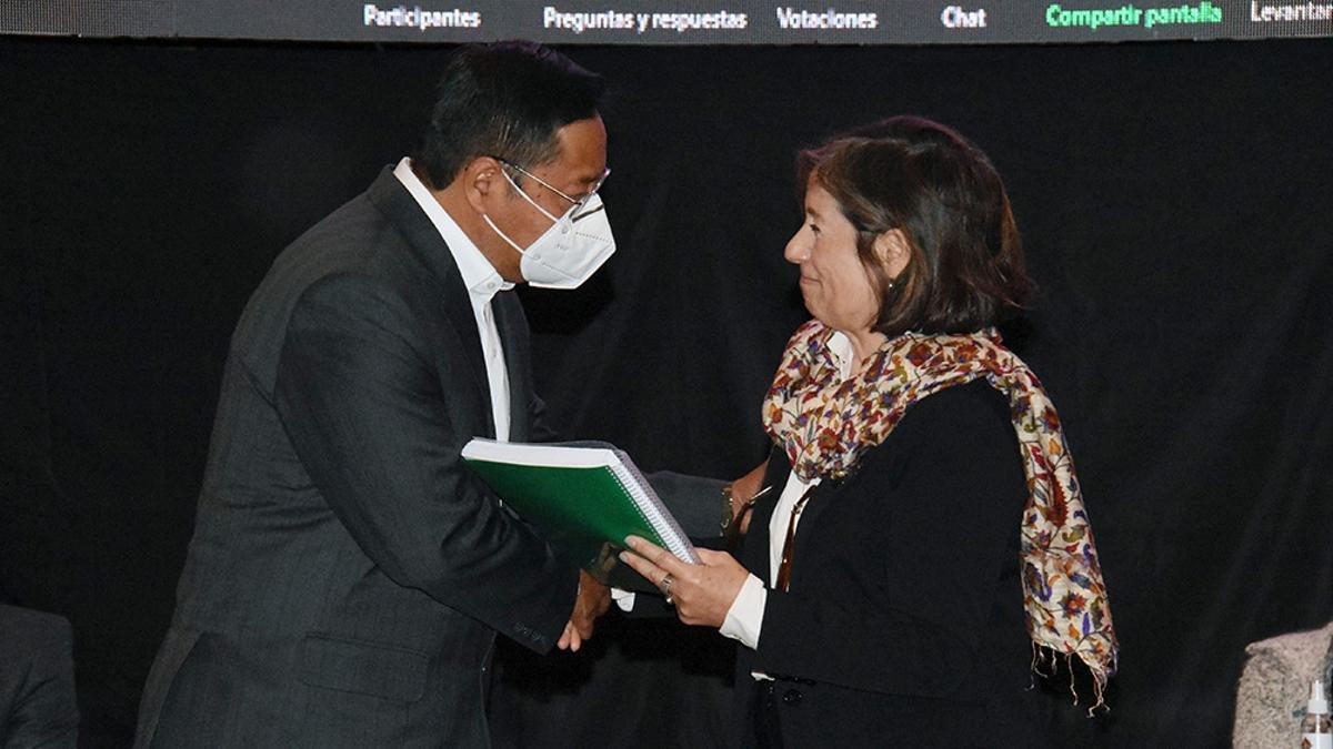 El presidente Luis Arce recibe el informe de manos de la representante del GIEI Patricia Tappatá.