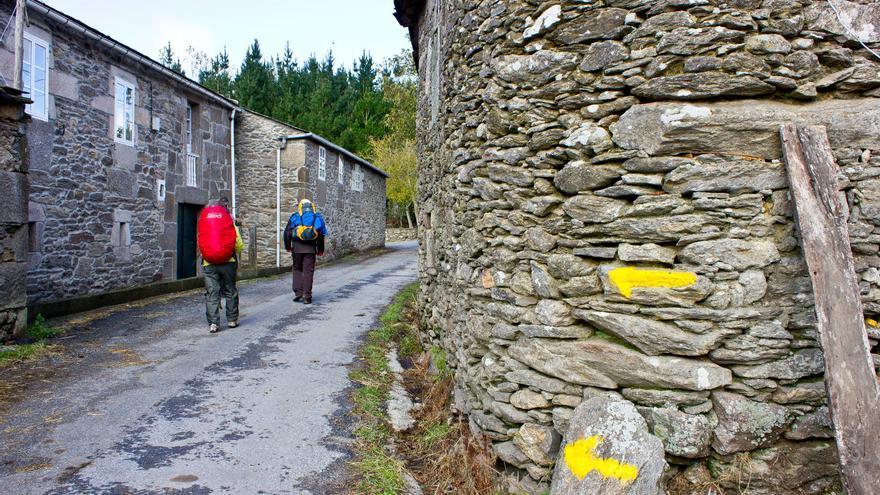 Flechas amarillas en los muros de una pequeña aldea del Camino de Santiago.