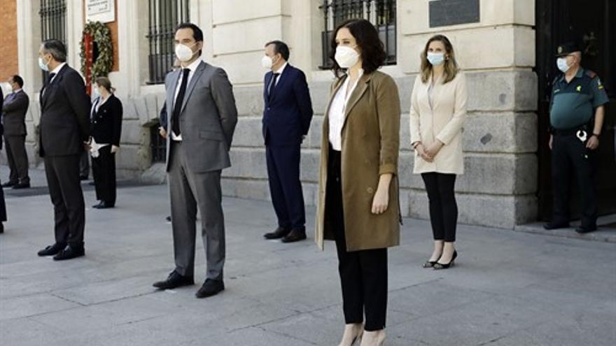 El vicepresidente de la Comunidad, Ignacio Aguado (4d); la consejera de Medio Ambiente, Paloma Martín (1d); y la Presidenta, Isabel Díaz Ayuso (2d), entre otros cargos del Gobierno de Madrid, guardan un minuto de silencio en memoria por los fallecidos por el COVID-19 en la sede de la Comunidad de Madrid.