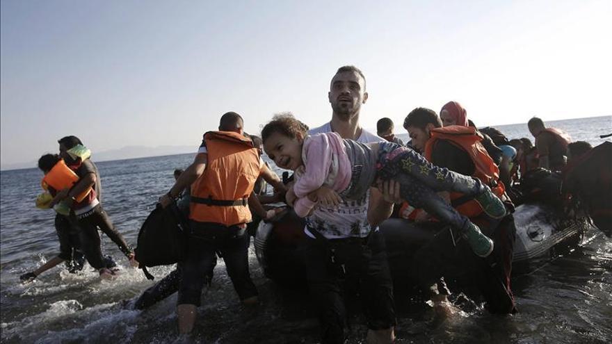 Un refugiado sirio lleva a una niña en brazos a su llegada en una lancha a la isla de Kos (Grecia) este mes de agosto.