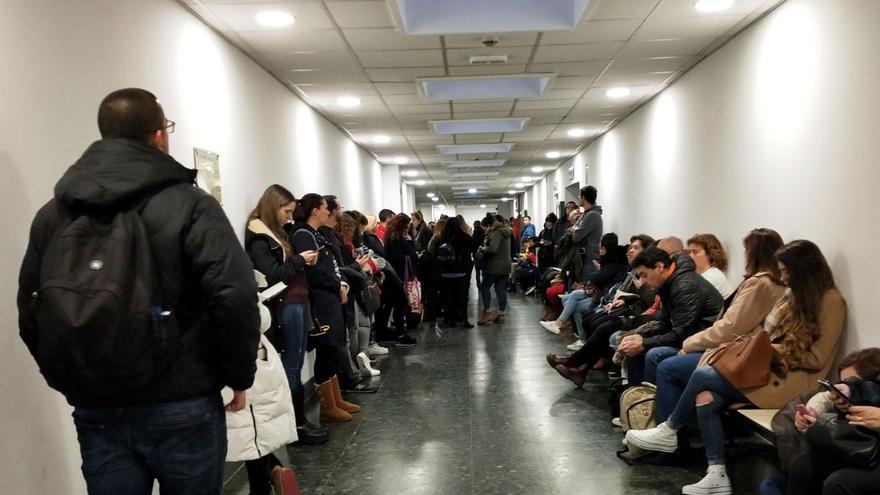 Decenas de personas esperan en un pasillo de la facultad de Ciencias Biológicas, antes de examinarse este domingo.