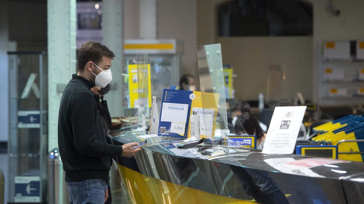 Un hombre es atendido en una oficina de Correos.