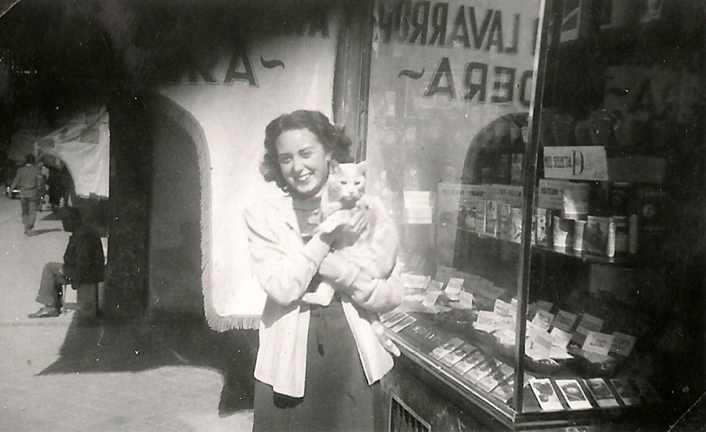 Una joven Marujita, con su gato Rubín, hacia 1950 en la puerta de Herboristería Angélica
