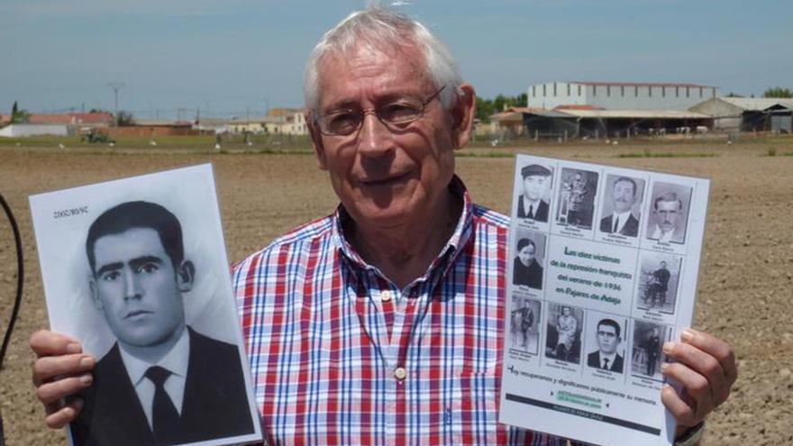 Pedro Fausto Canales con fotografías de las víctimas de Pajares ante el lugar donde fue encontrada la fosa.   FUEN BENAVENTE