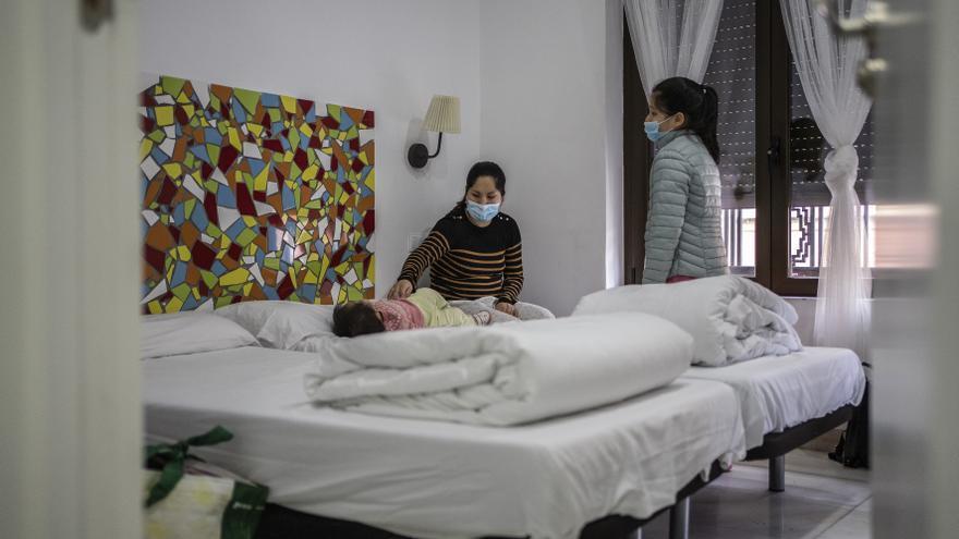 Ana cambia a su bebé junto a su hija mayor en la habitación del primer hostal donde fueron trasladados de forma temporal por Cruz Roja.