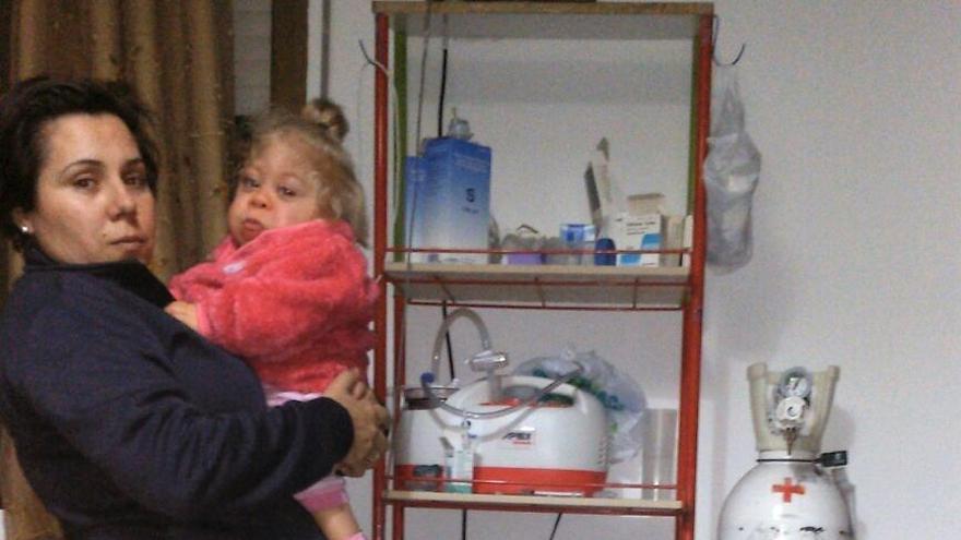 Elena posa con su hija ante algunos de los aparatos que necesita para sobrevivir.