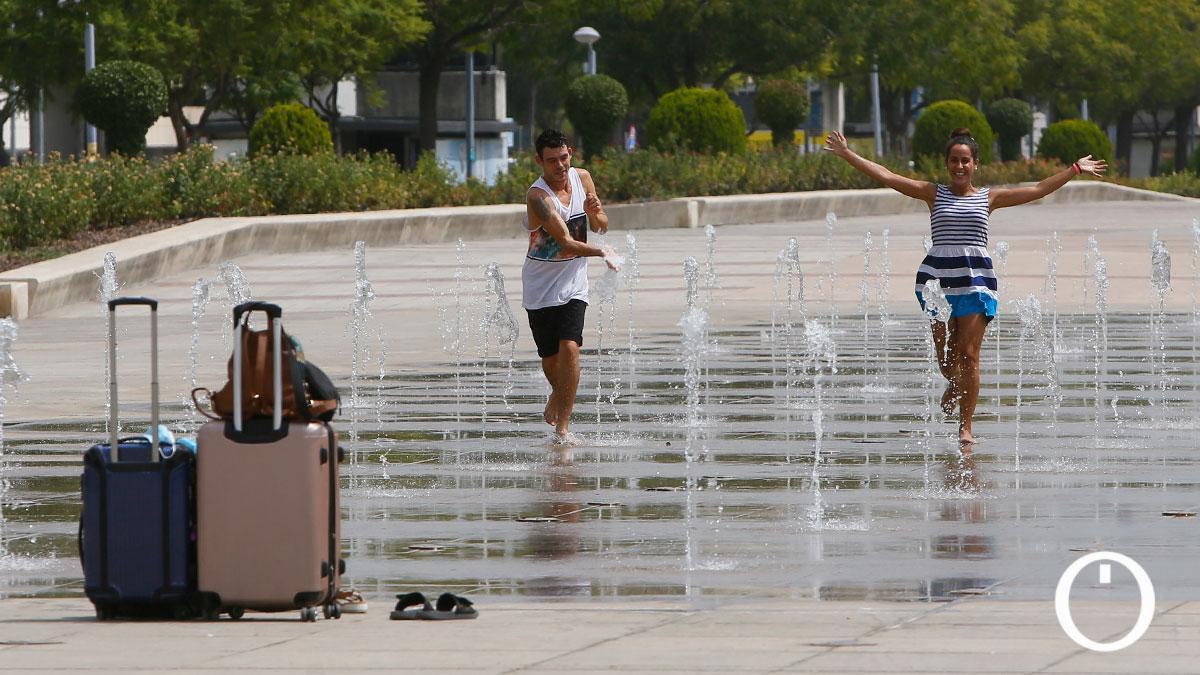 Unos turistas se refrescan en una fuente durante la ola de calor