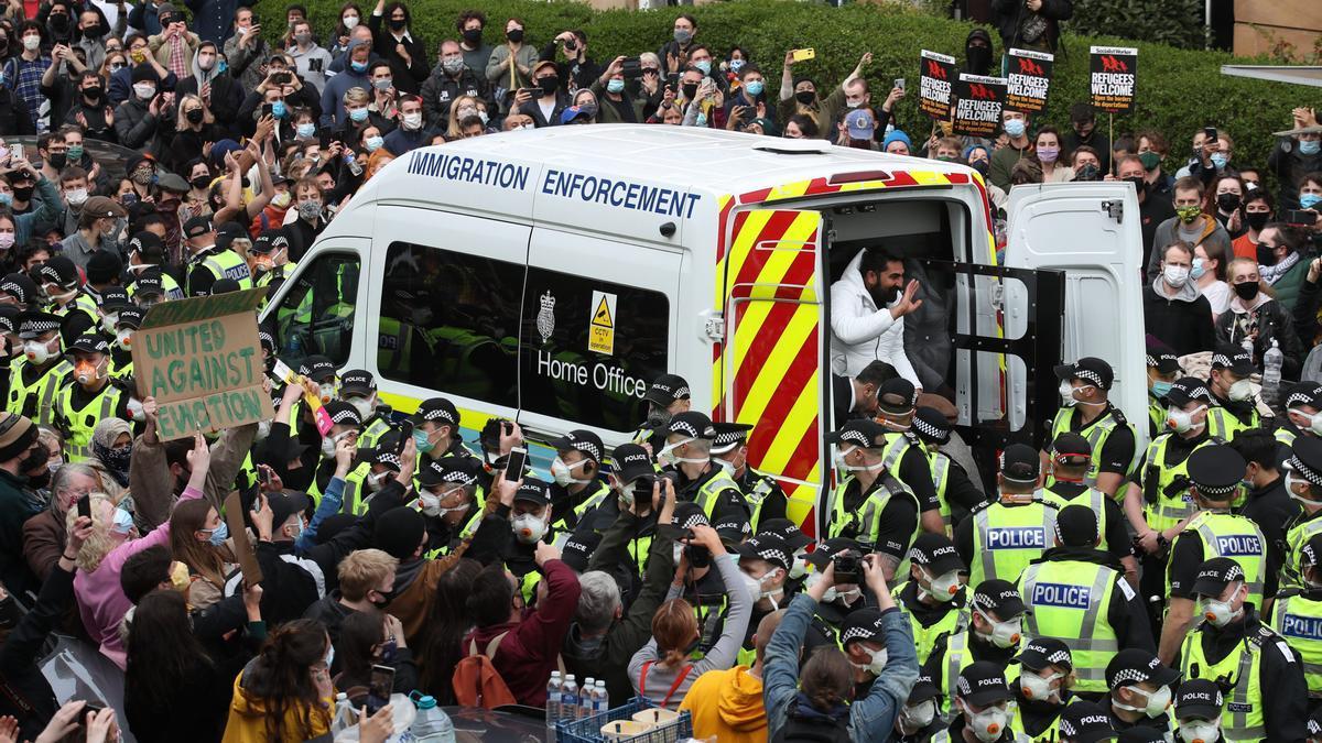 Uno de los dos hombres es liberado de la parte trasera de una furgoneta de las Fuerzas de Inmigración acompañado, en la calle Kenmure de Glasgow, que está rodeada de manifestantes.