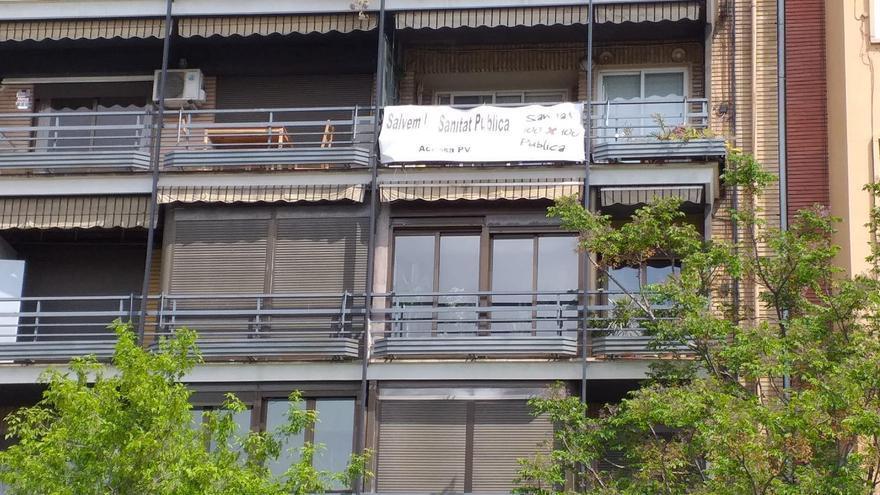Una sábana con un lema en favor de la sanidad pública en un balcón de València