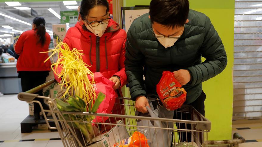 Dos personas con mascarillas hacen la compra en un supermercado de Beijing, China.