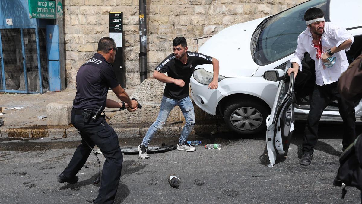 Un policía israelí apunta contra un palestino después de que un conductor fuese atacado por los manifestantes y posteriormente atropellase a algunos de ellos.