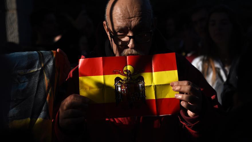 Un manifestante muestra una bandera preconstitucional durante el segundo entierro de Franco.