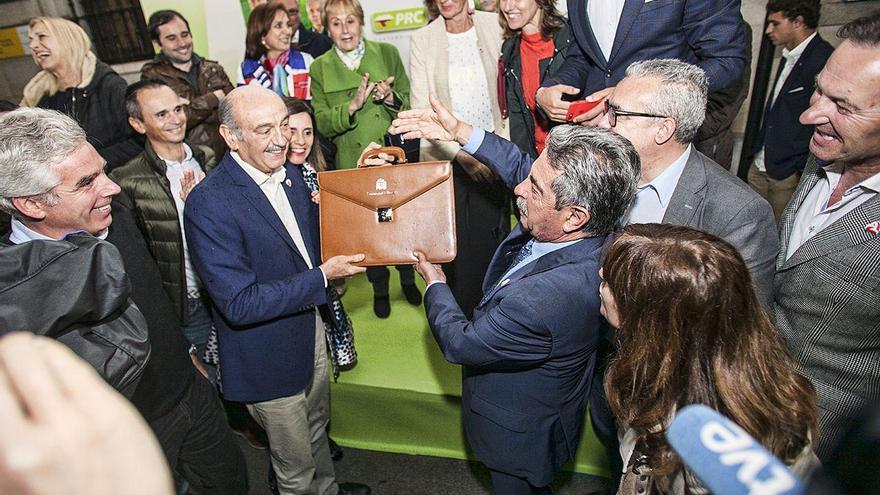 Mazón, recién llegado de Madrid, muestra la cartera de diputado que ha recogido en el Congreso.