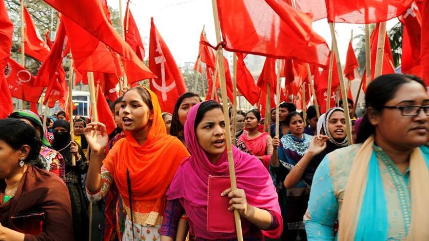 Trabajadoras de la industria textil portan banderas rojas mientras participan en una protesta organizada por la Federación Nacional de Trabajadores de la Industria Textil (NGWF) en Bangladesh.