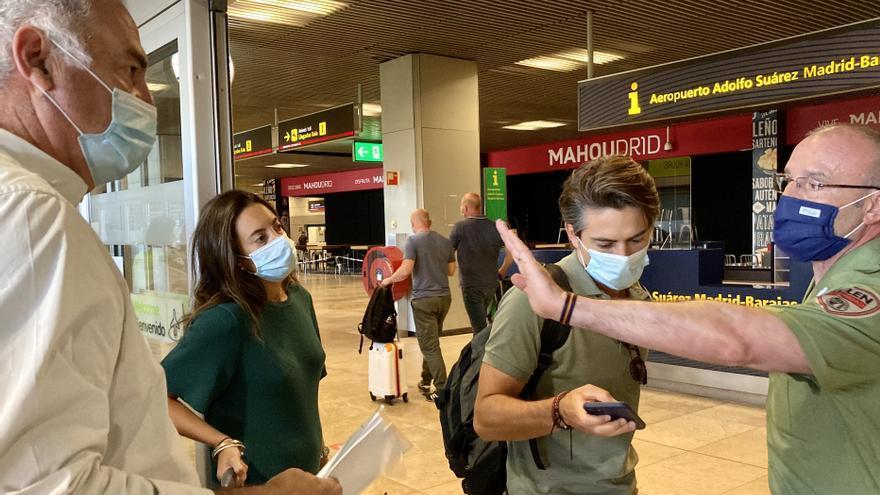 Un vigilante de seguridad pone orden a la entrada de la T1 entre los pasajeros y los familiares que esperan