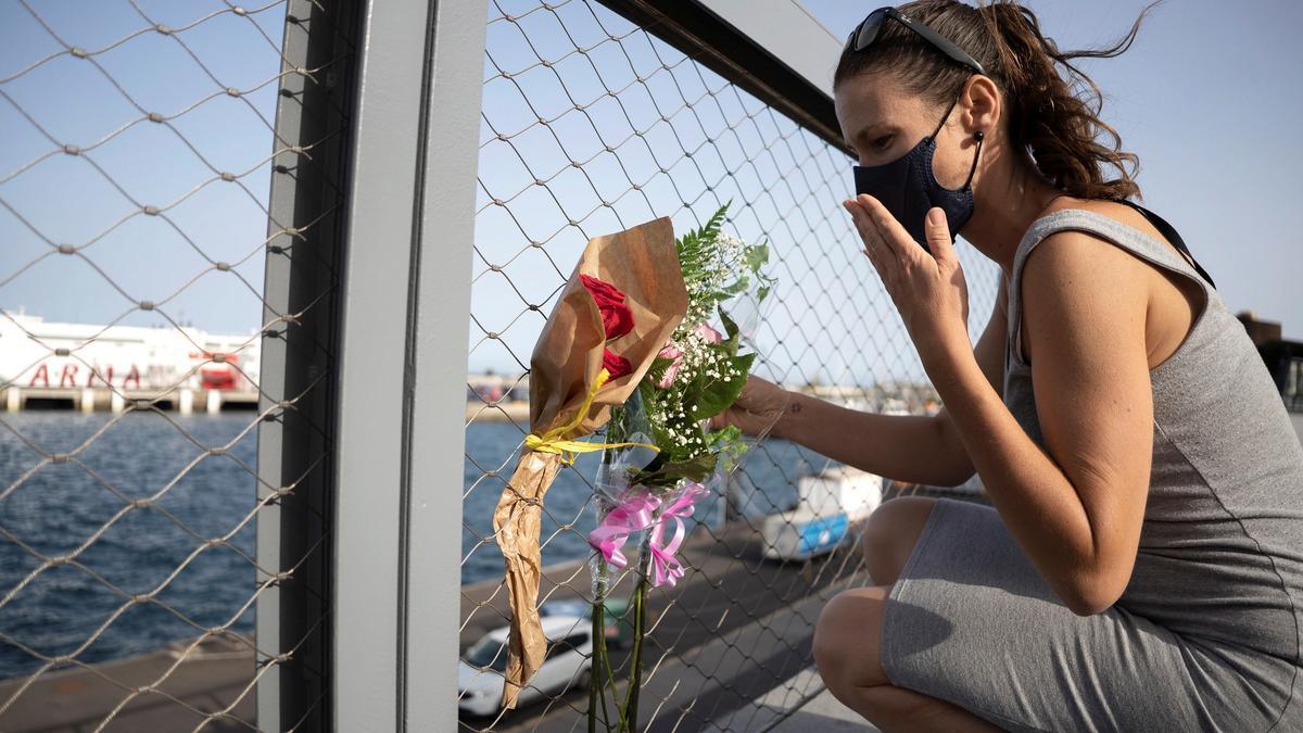 Una mujer coloca un ramo de flores frente al puerto de Santa Cruz, donde fue localizado el cuerpo de Olivia, una de las niñas desaparecidas en Tenerife