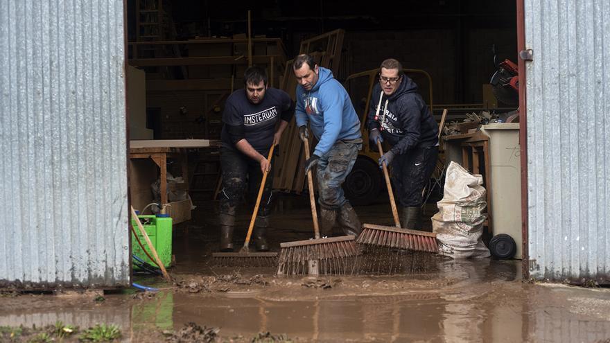 Tres vecinos se afanan en limpiar los destrozos causados por las inundaciones. | JOAQUÍN GÓMEZ SASTRE