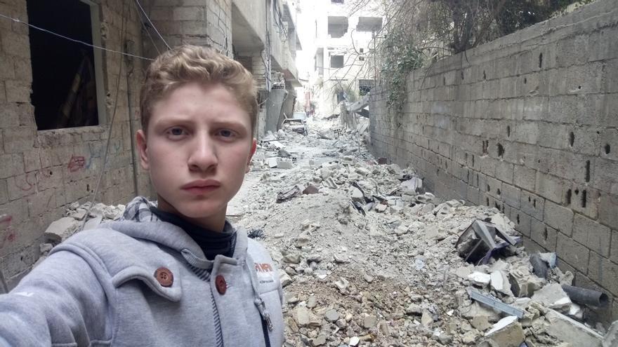 Muhammad Najem, de 16 años, se fotografía en una calle de Siria llena de escombros por los bombardeos.