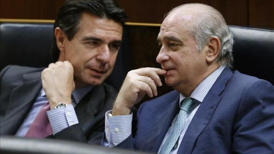 Los ministros de Industria, José Manuel Soria (izda), y del Interior, Jorge Fernández Díaz, conversan en sus escaños durante el pleno del Congreso.