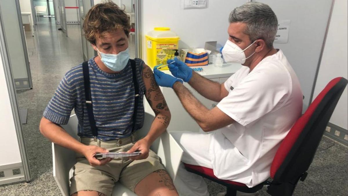 Un sanitari vacuna un jove a València.
