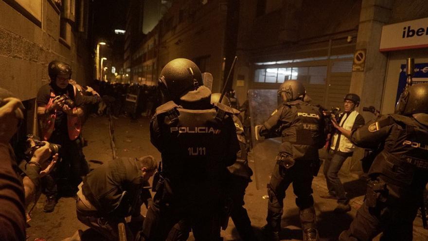 Agentes golpeando a manifestantes.