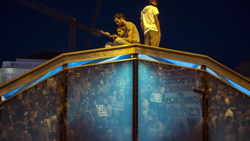 """Tres manifestantes se encaraman a la cúpula de entrada y salida al Metro de Sol, al finalizar la manifestación """"rodea el Congreso"""""""