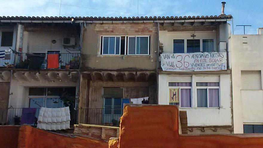 El solar en el que se construirán los apartamentos turísticos con una pancarte de protesta en el balcón de detrás