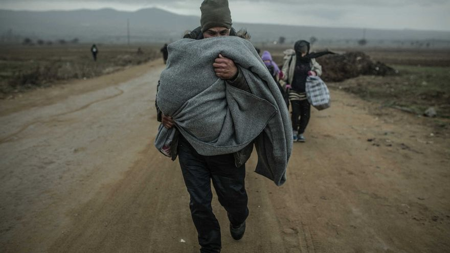 Khalid tries to protect his children from the cold along the route