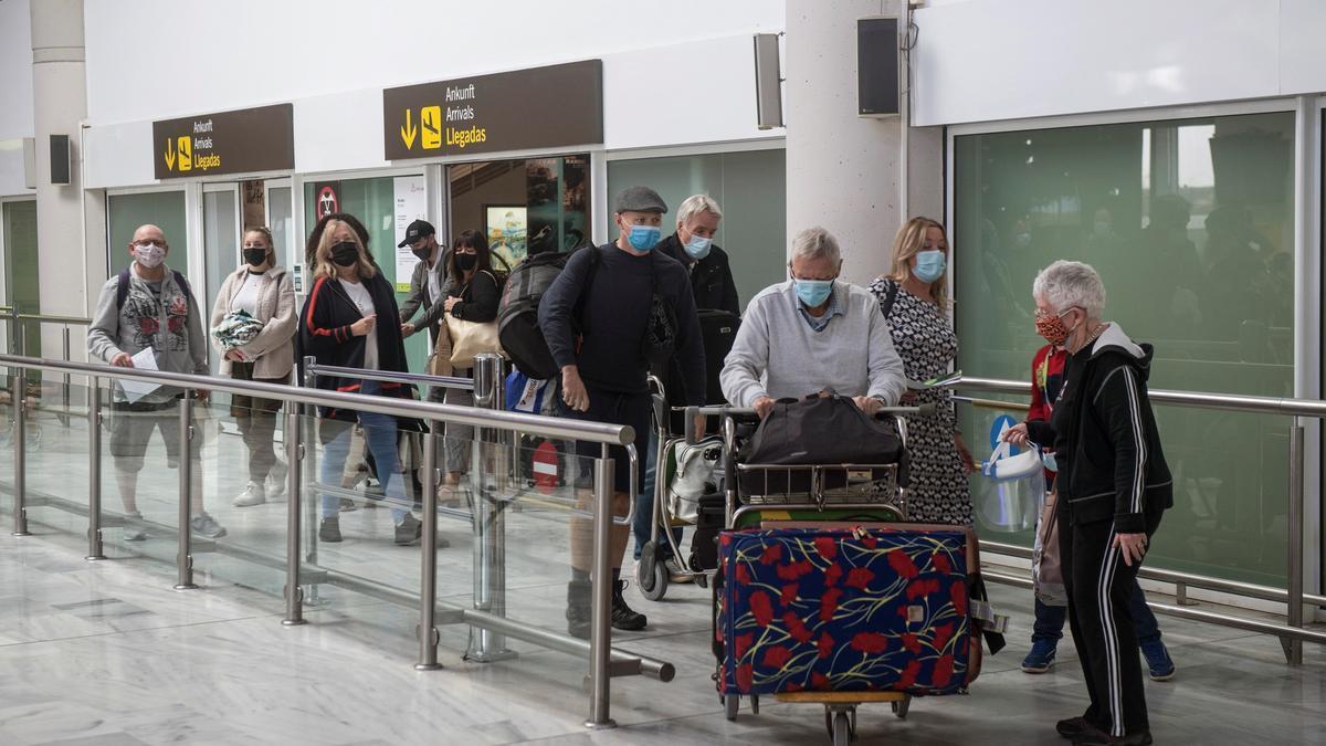 Varios turistas salen de la sala de recogida de equipajes a su llegada al aeropuerto César Manrique de Lanzarote. EFE/JAVIER FUENTES/Archivo