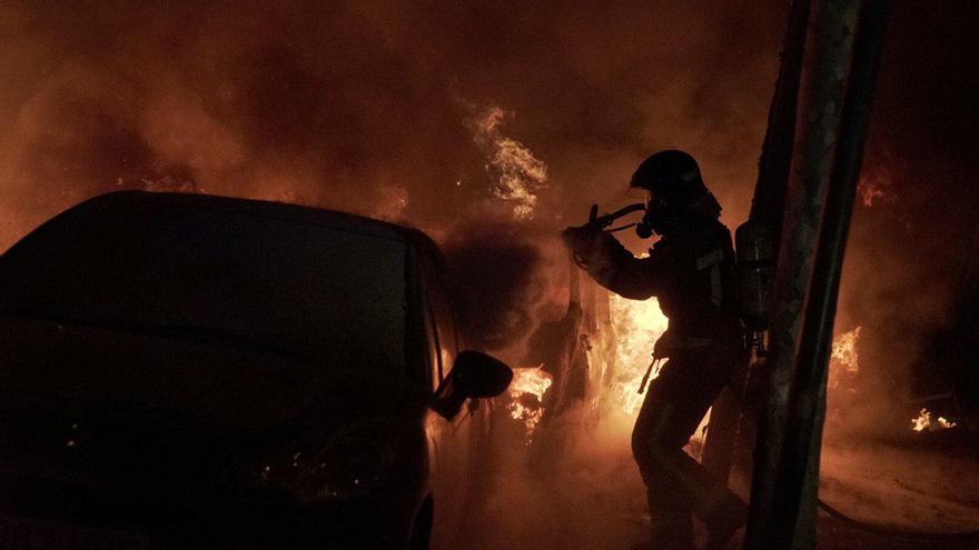 Un bombero apaga el fuego en un coche en los disturbios de Barcelona en la noche del 16 de octubre.